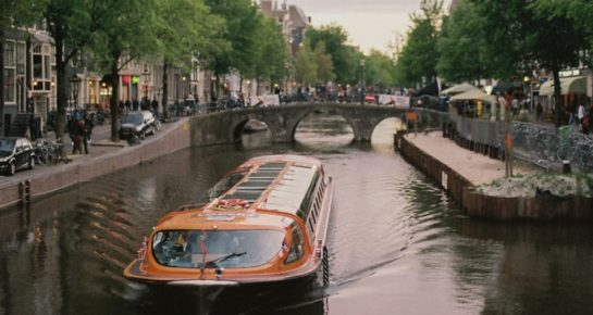 a boat sailing on a river in the center of Amsterdam