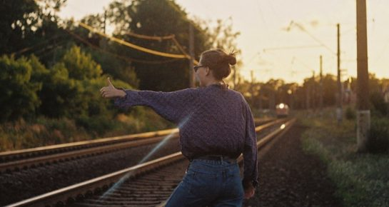 a standing girl next to a railway track passing by a train