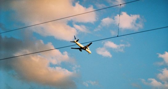 a flying plane near electrical wires in the blue sky