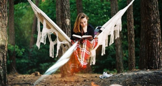 a girl sitting in a hammock and reading a book next to a campfire