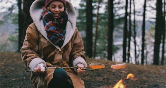 a girl baking sausages on a campfire in nature